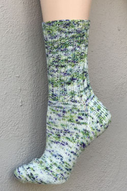 A speckled sock in shades of blue and green with a light green background on a foot form